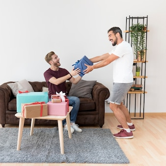 Aufgeregter junger mann, der zu hause eingewickelte geschenkbox seinem freund gibt