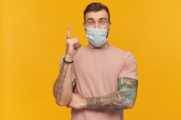 Aufgeregter junger mann im rosa t-shirt und in der virusschutzmaske im gesicht gegen coronavirus mit bart und tätowierung auf der hand, die nach oben zeigt und eine idee über gelber wand hat