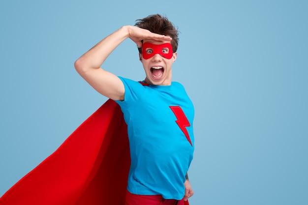 Aufgeregter junger mann im superheldenkostüm, das hand nahe stirn hält und kamera mit geöffnetem mund gegen blauen hintergrund betrachtet