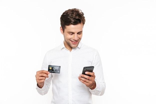 Aufgeregter junger mann mit dunklem haar, der smartphone und kreditkarte hält