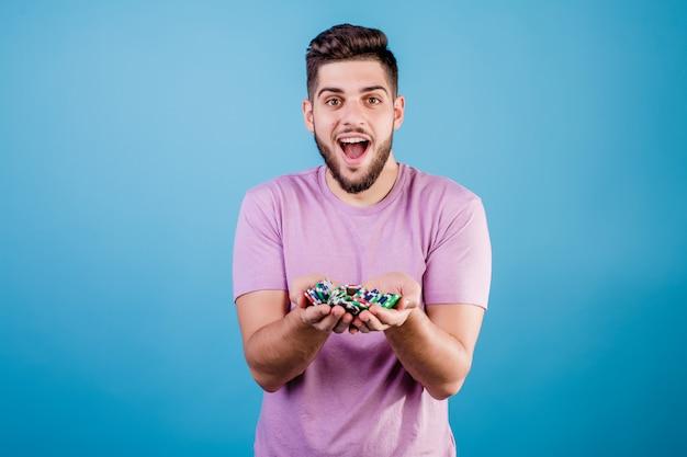 Aufgeregter junger mann mit einer handvoll pokerchips auf blau