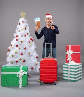 Aufgeregter junger mann mit koffer, der seine fahrkarten um weihnachtsbaum und geschenke auf grau zeigt