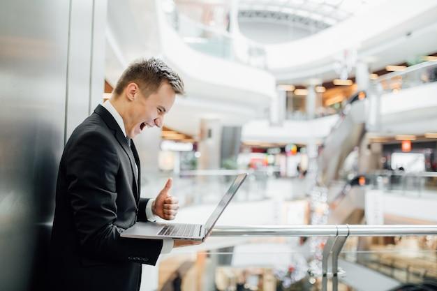 Aufgeregter junger mann mit laptop in der hand, der daumen hoch zeigt, glücklich, im schwarzen anzug gekleidet