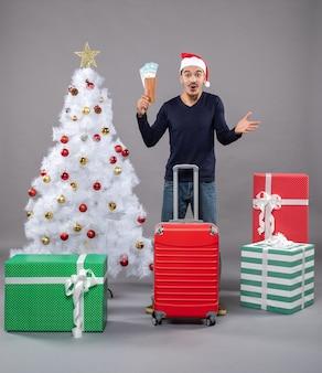 Aufgeregter junger mann mit reiseticket und rotem koffer um weihnachtsbaum und geschenke auf grau
