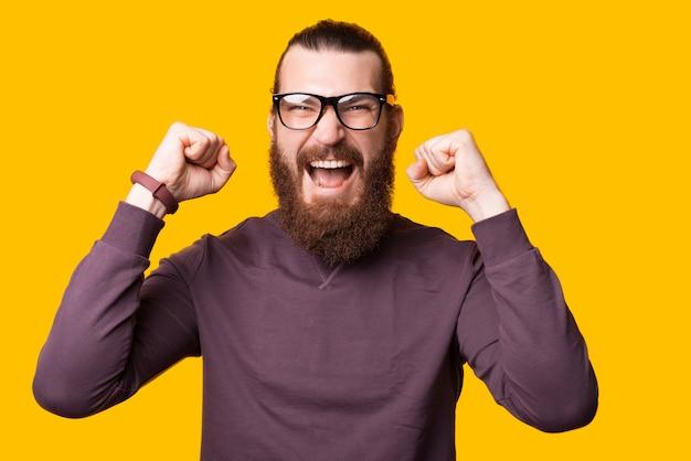 Aufgeregter junger mann schreit, weil er mit beiden händen mit brille in der nähe einer gelben wand aufgeregt ist