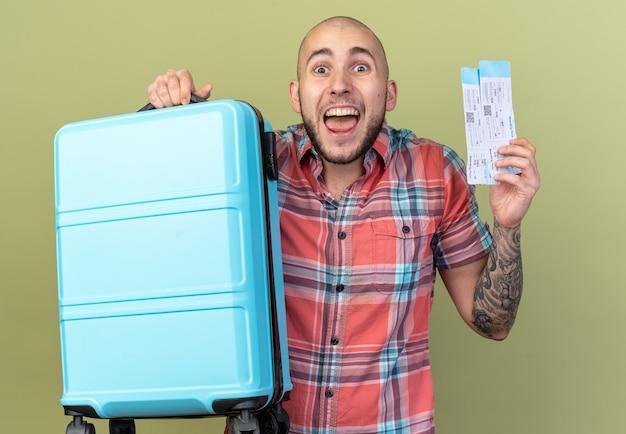 Aufgeregter junger reisender, der koffer und flugtickets isoliert auf olivgrüner wand mit kopierraum hält