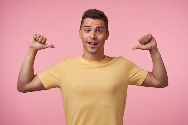Aufgeregter junger reizender braunäugiger brünetter mann, der fröhlich in die kamera schaut, während er sich mit erhobenen händen zeigt, isoliert über rosa hintergrund