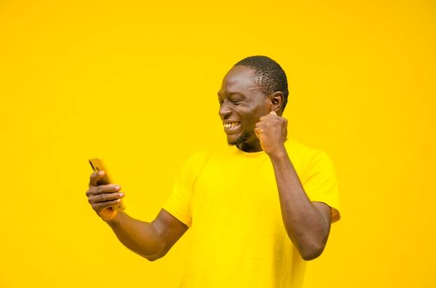 Aufgeregter junger schwarzer mann, der sich beim anzeigen von inhalten auf seinem smartphone aufgeregt fühlt und den gewinn feiert