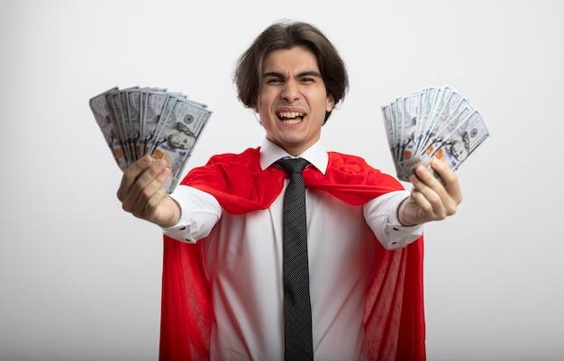 Aufgeregter junger superheld, der kamera betrachtet, die krawatte hält, die bargeld an der kamera lokalisiert auf weiß hält