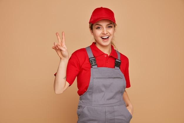 Aufgeregter junger weiblicher bauarbeiter, der uniform und kappe trägt, die hand in der tasche hält, die friedenszeichen tut