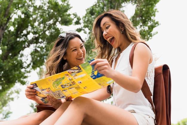 Aufgeregter junger weiblicher tourist, der unter dem baum betrachtet karte sitzt