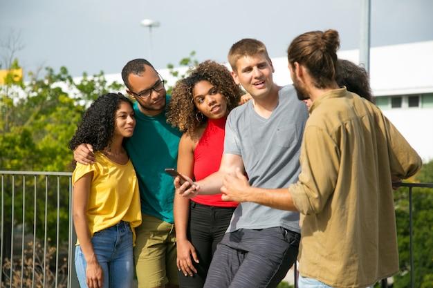 Aufgeregter kaukasischer kerl mit smartphone argumentierend mit männlichem freund