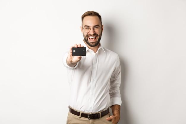 Aufgeregter kaukasischer mann in den gläsern, die kreditkarte, konzept des einkaufens zeigen.