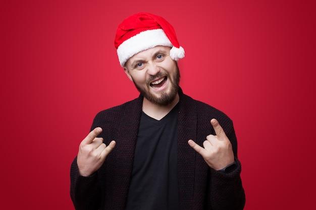Aufgeregter kaukasischer mann mit weihnachtsmütze, der rock'n'roll-zeichen auf einer roten studiowand gestikuliert
