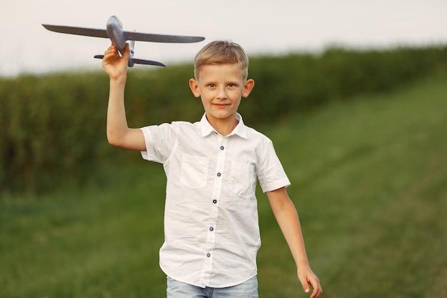 Aufgeregter kleiner junge, der mit einem spielzeugflugzeug läuft