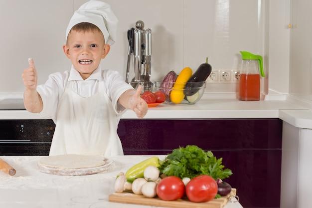 Aufgeregter kleiner junge, der pizza kocht und einen daumen hoch macht