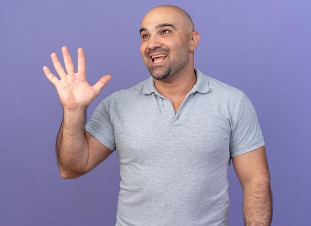 Aufgeregter lässiger mann mittleren alters, der nach oben schaut und fünf mit der hand isoliert auf lila wand zeigt