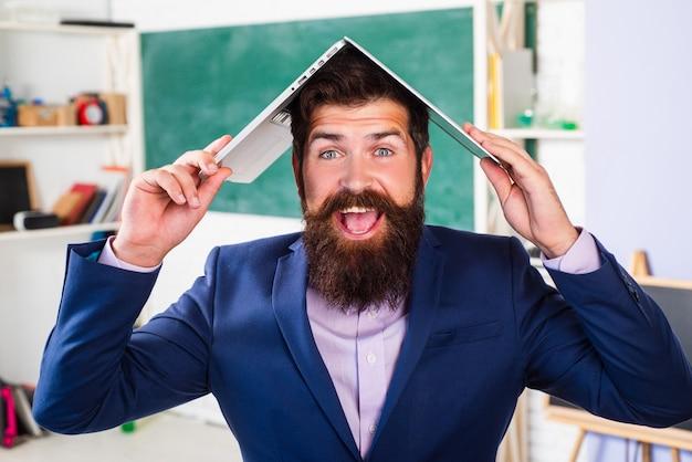Aufgeregter lehrerprofessor mit laptop auf dem kopf, der formellen anzug mit lustigen ausdrucksgefühlen lustiges gesicht trägt.