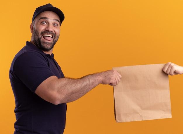Aufgeregter lieferbote mittleren alters in uniform und mütze, die dem kunden lebensmittelverpackung aus papier geben, isoliert auf gelber wand