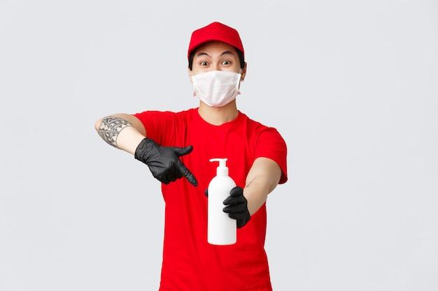 Aufgeregter lieferer, der auf die handdesinfektionsflasche zeigt und die kamera schaut, gewährleistet die sicherheit von kunden und mitarbeitern während des ausbruchs des covid-19-virus. kurier in medizinischer maske und handschuhen arbeiten