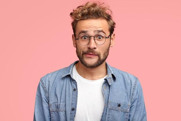 Aufgeregter lockiger hipster mit verwirrtem ausdruck spitzt lippen und sieht mit fassungslosem ausdruck aus, trägt jeanshemd, hat stoppeln, isoliert über rosa wand. menschen-, reaktions- und lifestyle-konzept