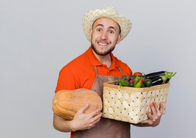 Aufgeregter männlicher gärtner, der gartenhut trägt, hält kürbis und gemüsekorb suchen