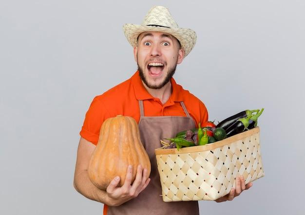 Aufgeregter männlicher gärtner, der gartenhut trägt, hält kürbis und gemüsekorb