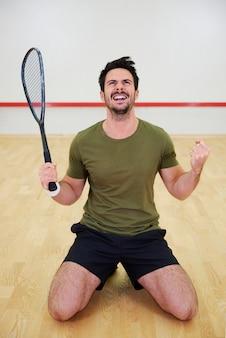 Aufgeregter männlicher squashspieler, der auf dem platz feiert