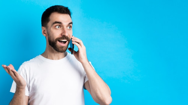 Aufgeregter mann, der auf smartphone spricht