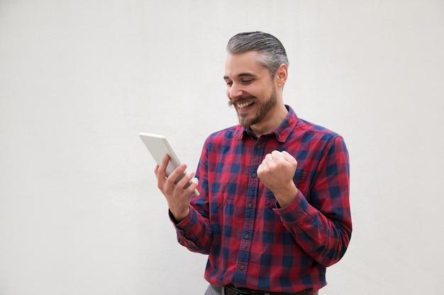 Aufgeregter mann, der digitale tablette verwendet