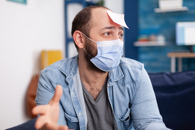 Aufgeregter mann, der ein namensspiel mit multiethnischen freunden spielt, die eine gesichtsmaske tragen, um soziale distanz zu wahren, weil die soziale pandemie spaß hat. konzeptionelles bild.