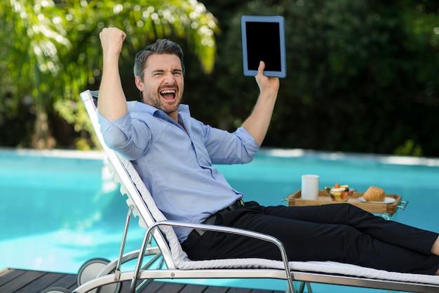 Aufgeregter mann, der eine digitale tablette nahe pool hält