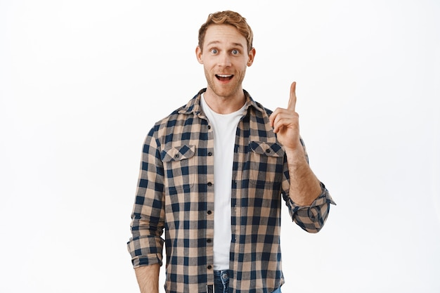 Aufgeregter mann, der eine großartige idee vorbringt, erfreut lächelt und den finger hebt, um etwas geniales zu sagen, einen plan hat, einen vorschlag hat und über der weißen wand steht?