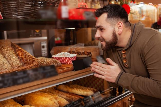 Aufgeregter mann, der gebäck in der örtlichen bäckerei einkauft und die vitrine betrachtet
