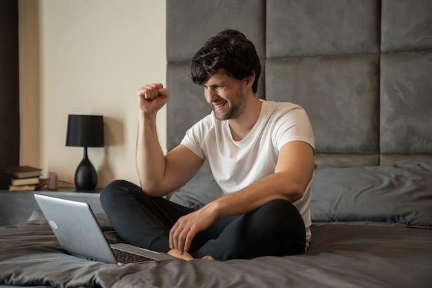 Aufgeregter mann, der mit einem laptop auf einem bett sitzt, feiert erfolg