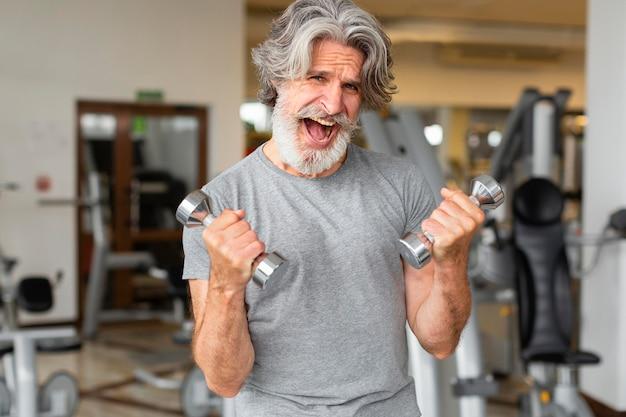 Aufgeregter mann, der mit hanteln trainiert