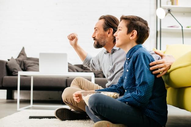 Aufgeregter mann, der mit seinem glücklichen sohn sitzt und eine faust hochlegt, während er zu hause ein erstaunliches sportspiel im fernsehen sieht