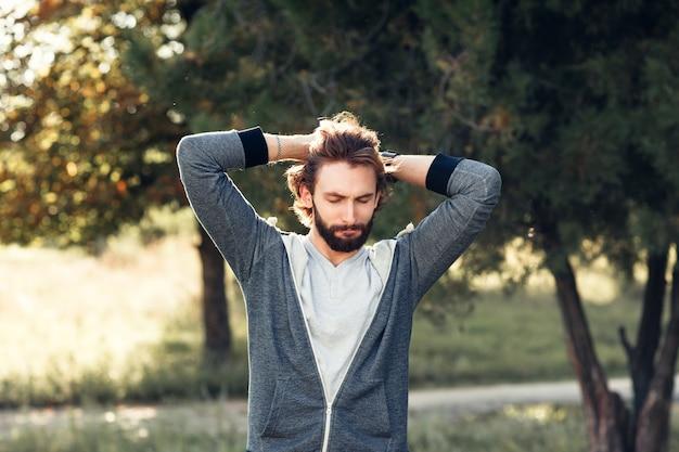 Aufgeregter mann, der seinen kopf im park berührt.