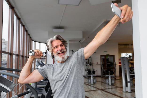Aufgeregter mann, der selfies im fitnessstudio nimmt