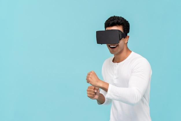 Aufgeregter mann, der video von vr-gläsern aufpassend genießt