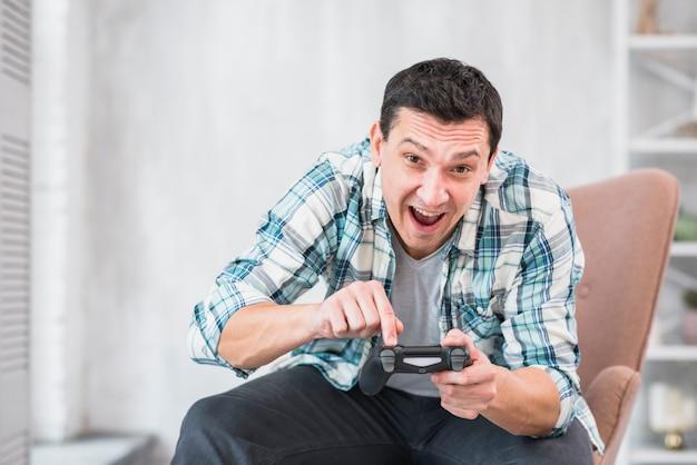 Aufgeregter mann, der zu hause mit gamepad spielt