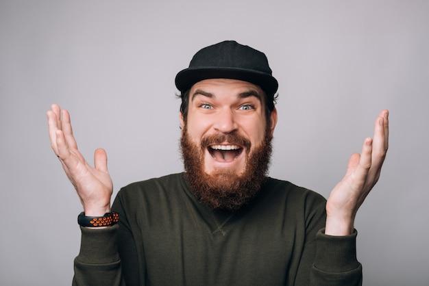 Aufgeregter mann hält hände in der luft und lächelt in die kamera.