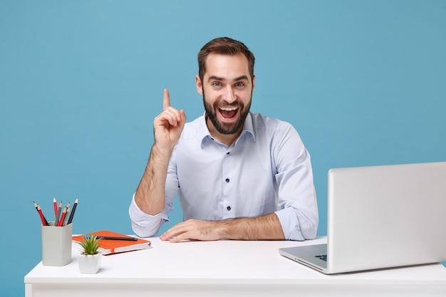Aufgeregter mann im hellen hemd sitzen arbeit am schreibtisch mit pc-laptop lokalisiert auf blauer wand. achievement business karriere lifestyle-konzept. halten sie den zeigefinger mit einer großartigen neuen idee hoch.