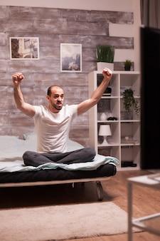 Aufgeregter mann im schlafzimmer, der sport im großen fernsehen ansieht.
