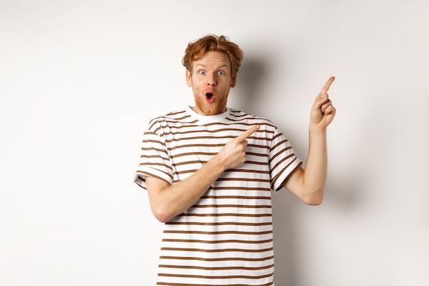 Aufgeregter mann mit dem gelockten roten haar, das promo-angebot zeigt und erstaunt schaut, finger auf logo der oberen rechten ecke zeigend, weißer hintergrund.
