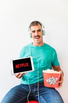 Aufgeregter mann mit dem popcorn, das netflix-logo zeigt