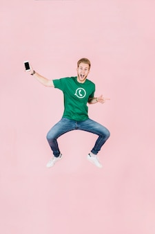 Aufgeregter mann mit dem smartphone, der auf rosa hintergrund springt