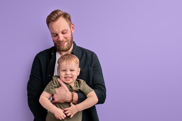 Aufgeregter mann mit kind junge in den händen, im studio auf lila hintergrund posierend.