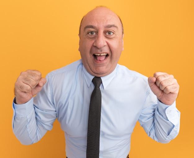 Aufgeregter mann mittleren alters, der ein weißes t-shirt mit krawatte trägt und eine ja-geste zeigt, die auf oranger wand isoliert ist
