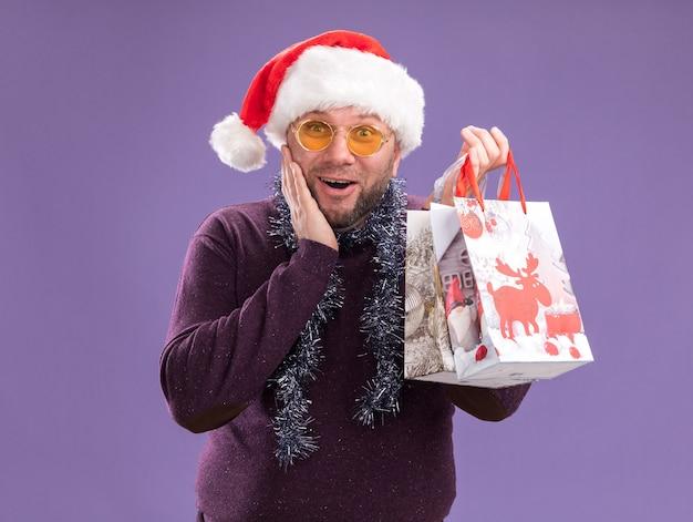 Aufgeregter mann mittleren alters, der weihnachtsmütze und lametta-girlande um den hals mit gläsern hält, die weihnachtsgeschenktüten halten, die kamera betrachten, die hand auf gesicht lokalisiert auf lila hintergrund hält